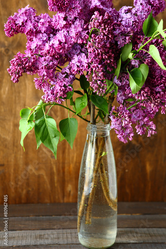 Foto op Canvas Lilac Bouquet of lilac in a vase on the boards
