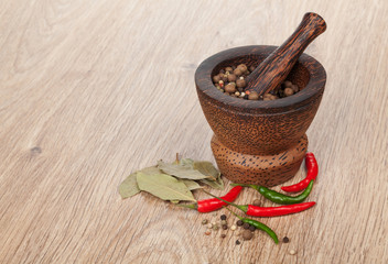 Mortar and pestle with red hot chili pepper and peppercorn