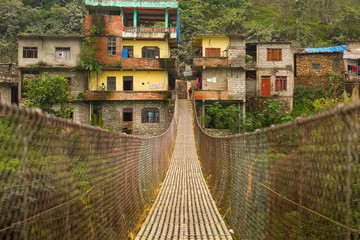 Rope hanging suspension bridge in Nepal with colorful village in