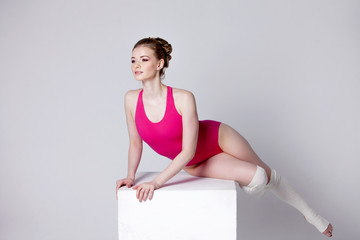 dancer. attractive young woman gymnast on a white cube