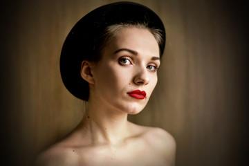Beautiful woman in black hat. Retro fashion.