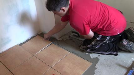 Construction worker tiler place floor tiles. Left side sliding