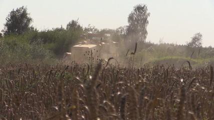 farm harvester working in grain field on summer day.