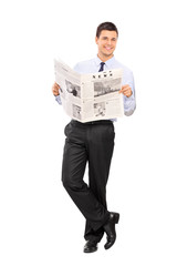 Man holding newspaper and leaning on a wall