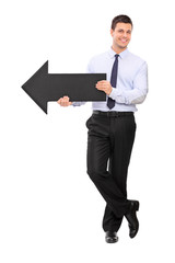 Young businessman holding black arrow pointing right
