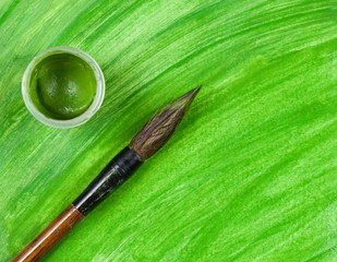 Artist's paintbrush tool with cup of green paint on artistic
