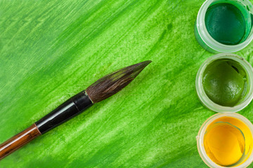 Green artistic watercolor painting with artist's paintbrush