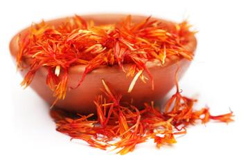 Safflower petals on a brown bowl