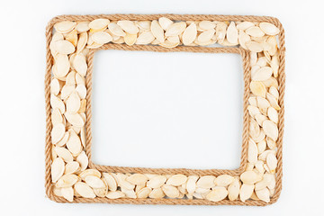 Two frames made of the rope with pumpkin seeds on a white backgr