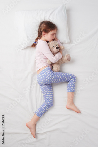 Top view of little cute girl sleeping with teddy bear - 80976488