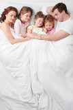 Family of five sleeping under blanket