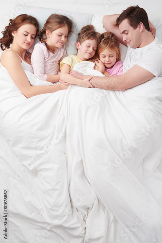 Family of five sleeping under blanket