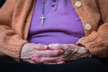 old woman's hands joined