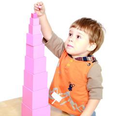 Little boy builds a pink tower.