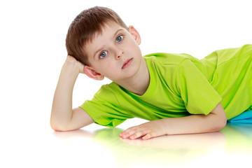 Little boy in green t-shirt lying on the floor.