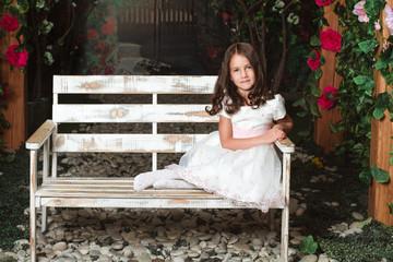 cute little girl sitting in the flowered garden