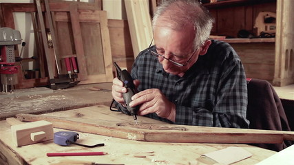 Senior carpenter carving wood with engraver tool