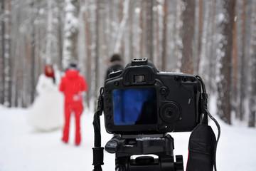 Wedding and camera. Blurred bride and groom. Winter season