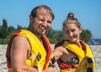 Pair puts on swimming waistcoats on beach