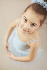 Little ballerina girl posing in ballet studio