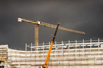 Hochbau und Kräne - Ein Unwetter zieht auf über einer Baustelle