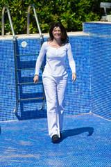 Gehende Frau im leeren Schwimmbecken