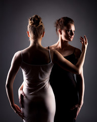 Portrait of sexy female dancers hugging in studio