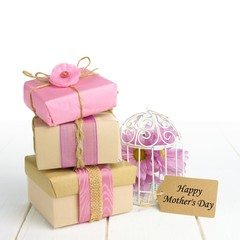 Stacked gift boxes with Happy Mother's Day tag and bird cage