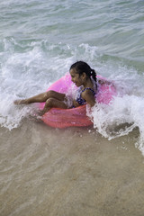 little girl floating on a pink raft