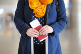 Woman holding passport and boarding pass