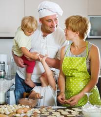 Happy family of four making meat dumplings