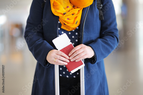 Woman holding passport and boarding pass - 80991817