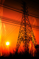 High voltage pole with a flame burning sunset