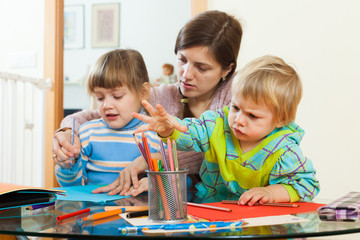 Mother and children sketching with pencils
