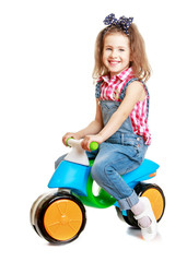 Laughing little girl riding a small bike.