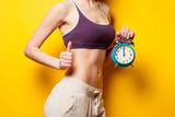 Woman showing her abs with alarm clock