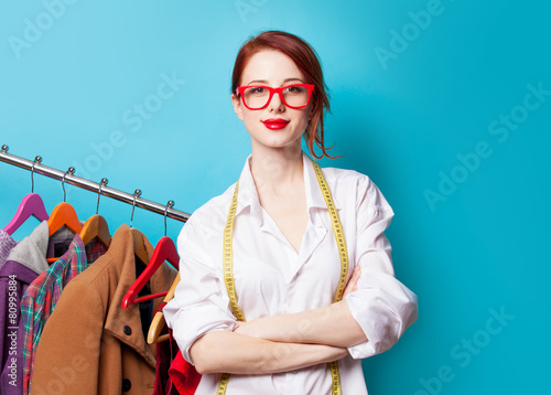 Young redhead designer with metric and clothes Poster