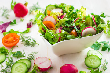 Healthy salad with fresh vegetables and ingredients on white bac