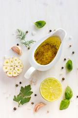 ingrediets for salad dressing. Olive oil, garlic, lemon, herbs a