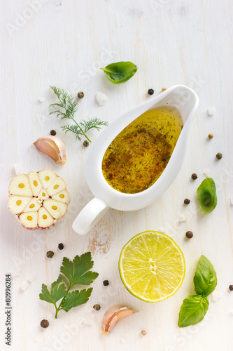Fotobehang Kruiderij ingrediets for salad dressing. Olive oil, garlic, lemon, herbs a