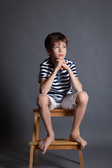 Portrait of serious pensive sad teenager on chair