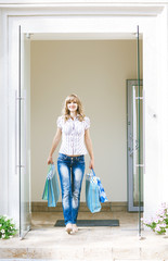 Woman at shop doors with shopping bags