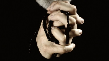 Hands praying black rosary