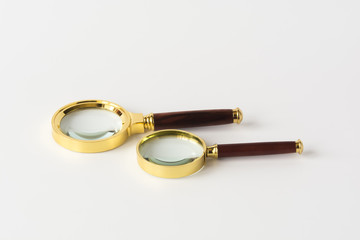 Two golden framed magnifying glasses