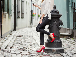 Woman standing in old town and using mobile phone