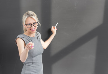 Teacher pointing at camera while writing on blackboard