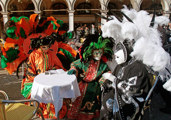 masked persons in colorful costume with plumage sitting in cafe