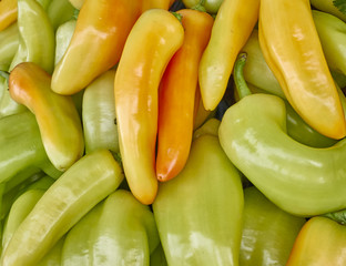 green and orange horn peppers closeup