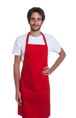 Entspannter Kellner mit Bart und roter Schürze