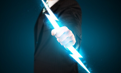 Business man holding glowing lightning bolt in his hands